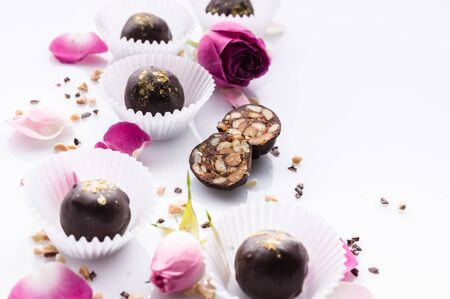 Chocolate candies with nuts and honey. Gourmet chocolates on a white background. Close-up. Soft focus. Copy space