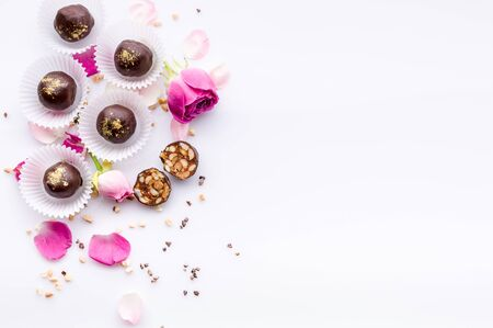 Sweet pattern. Top view handmade chocolate candies with nuts and honey. Gourmet chocolates on a white background. Close-up. Soft focus. Copy space Reklamní fotografie