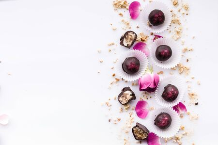 Sweet pattern. Top view handmade chocolate candies with nuts and honey. Gourmet chocolates on a white background. Close-up. Soft focus. Copy space Stok Fotoğraf