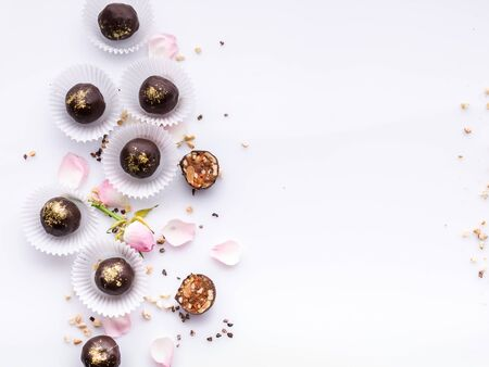 Confectionery pattern. Top view handmade chocolates with peanuts and honey. Gourmet chocolates on a white background. Close-up. Soft focus. Copy space