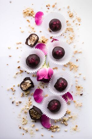 Top view vertical shot handmade chocolates with nuts and honey on a white background with rose petals.