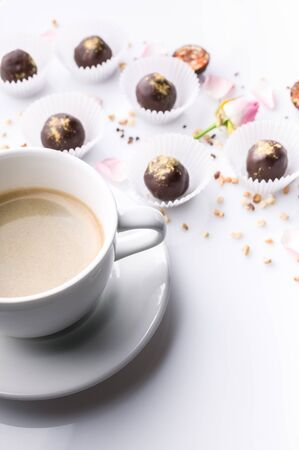 White ceramic cup of coffee and chocolate candies with handmade nuts on a white background. Vertical shot Reklamní fotografie