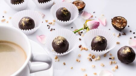 Food banner. White ceramic cup of coffee and chocolate candies with handmade nuts on a white background.