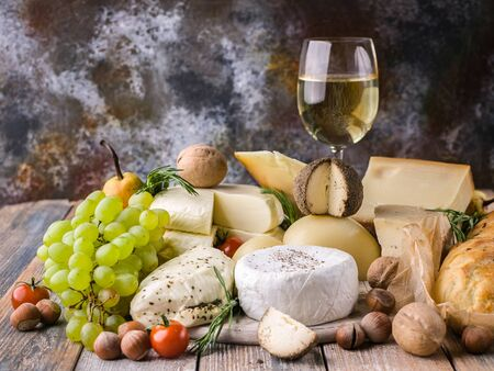 Food still life: Different types delicious cheeses, glass of white wine, nuts, fruits, spicy herbs and onion baguette on a rustic background. Stock fotó