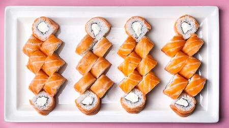 Philadelphia roll with salmon, cream cheese, rice and nori seaweed on a large rectangular white plate on a pink background. Top view