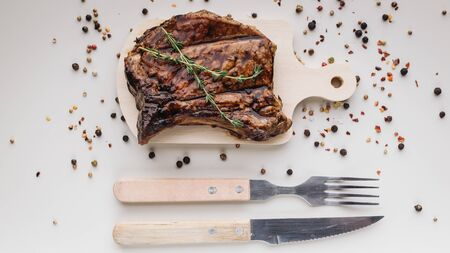 Appetizing medium rar grilled t-bone steak on a wooden cutting board on a light background with spices. Horizontal shot Stock Photo