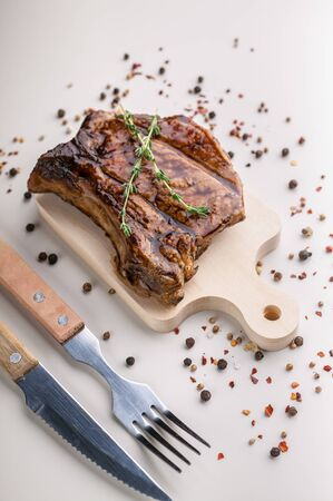 Vertical shot appetizing medium rar grilled t-bone steak on a wooden cutting board on a light background with spices