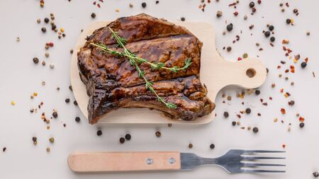 Food banner: appetizing medium rar grilled t-bone steak on a wooden cutting board on a light background with spices. Horizontal shot