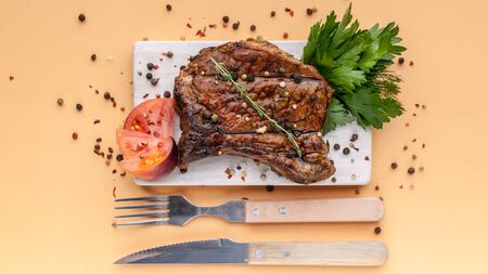 Food banner: medium rare grilled t-bone steak with spices and herbs on a wooden cutting board on a light background