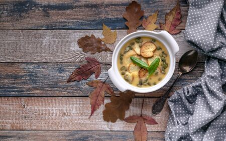 Autumn cream soup with vegetables, croutons, pumpkin seeds and fresh spinach on a rustic background. Top view. Copy space
