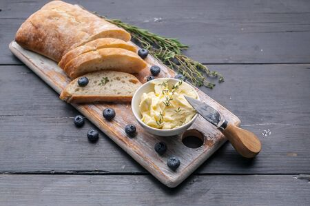 Baguette on a cutting board, butter and blueberries on a wooden table. Top view Stock Photo
