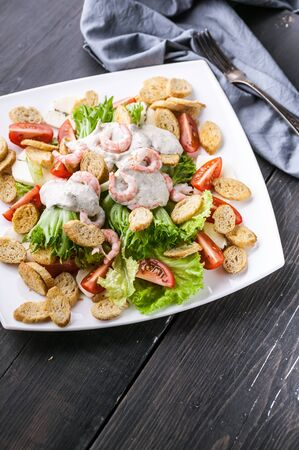 Vertical shot appetizing salad with shrimp, lettuce, cheese, avocado and crackers on a white plate. Delicious and healthy seafood recipes. Low calories