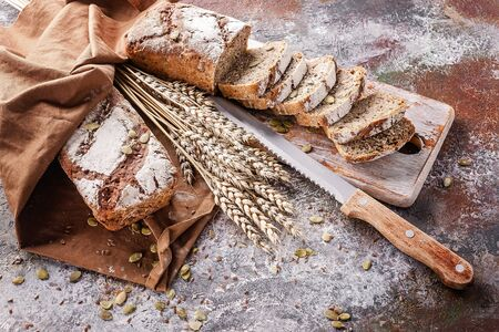 Freshly baked sourdough bread with sunflower and pumpkin seeds on a brown napkin. Sliced bread on a wooden board and a kitchen knife. Ears of wheat. Zdjęcie Seryjne
