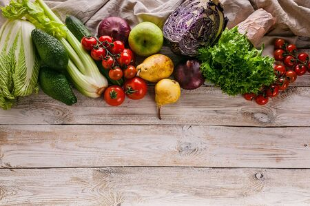 Top view border of tasty and healthy vegetables and fruits on a light rustic background. Copy space