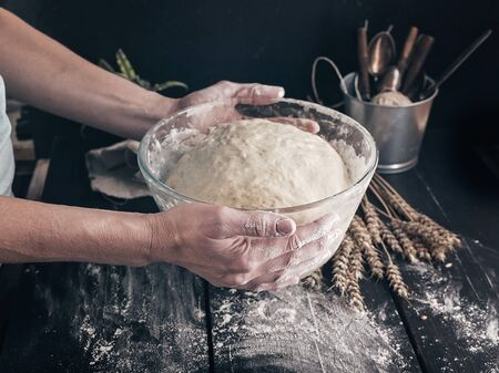 Female hands hold fermented homemade pastry for buns. Close-up. Step by step recipe Stockfoto