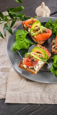 Vertical food banner. Delicious bruschettas with smoked salmon, curd cheese, avocado, basil and chia seeds. Tasty and healthy breakfast or snack. Mediterranean Kitchen. Close up Foto de archivo
