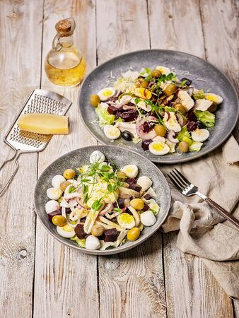Vertical shot squid salad with ice lettuce, sweet onions, sheeps spicy cheese, quail eggs, olives, micro-greens and olive oil. Mediterranean cuisine. Diet food. Copy space