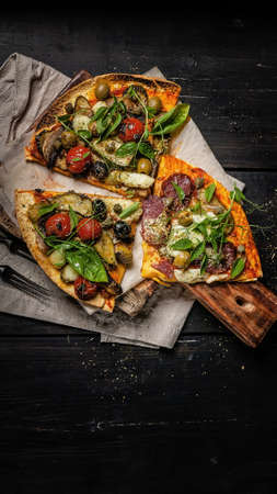 Vertical food banner. Delicious pizza with vegetables, mozzarella, olives and herbs on a cutting board on a dark background. Mediterranean Kitchen. Top view