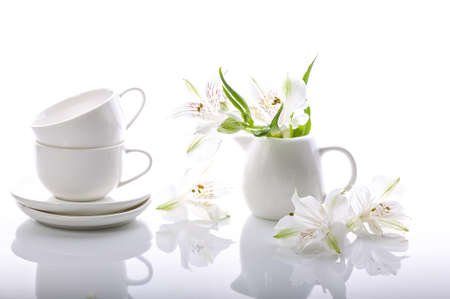Graceful white flowers and coffee set on a glossy background. Alstrameria, two cups and a milk jug. Still life Reklamní fotografie