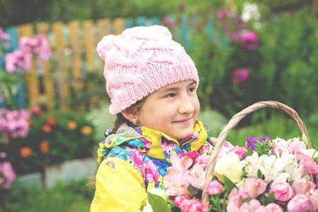 Cute young girl holding a basket with flowers. Lifestyle photo