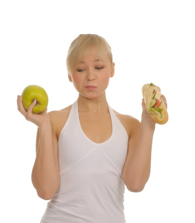 slim woman choosing between apple and hamburger  isolated on white  photo
