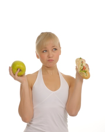slim woman choosing between apple and hamburger. isolated on white photo