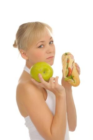 slim woman choosing between apple and hamburger. isolated on white photo