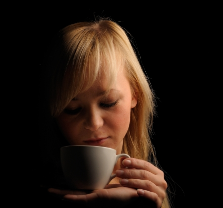 young blond hair woman with coffe  on a dark background.