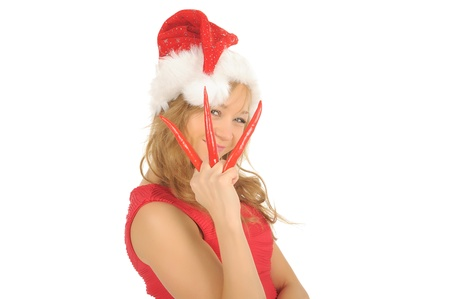Attractive young woman in Santa Cap with chili pepper. isolated on white. photo