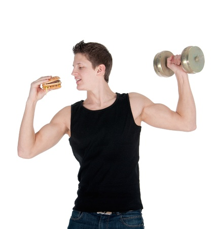 Handsome muscular man eats a hamburger while doing bicep curls. 版權商用圖片
