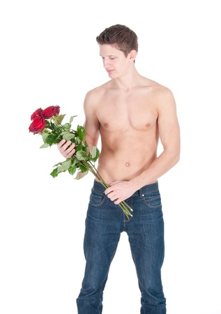 sexy young man with bared torso and bunch of a red roses on a white background. photo