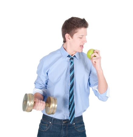 Young business man with dumbbell eating green apple. photo