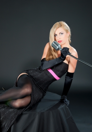 Portrait of a beautiful blonde woman in black dress and gloves with a retro microphone. photo