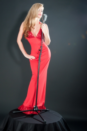 Portrait of a beautiful blonde woman in red dress and black gloves with a retro microphone. photo