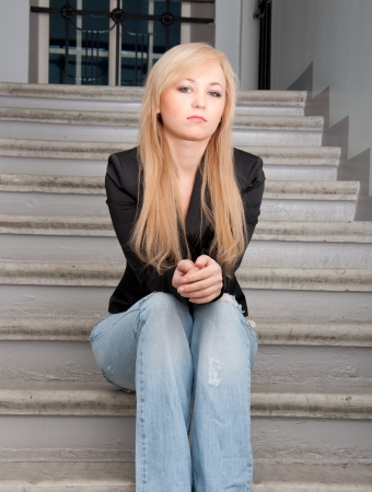 Sexy woman wearing blue jeans sitting on a stairs. photo