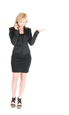 Young businesswoman in black  with smartphone posing over white background. photo