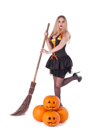 Halloween witch in black dress with pumpkin, broom.Isolated. photo