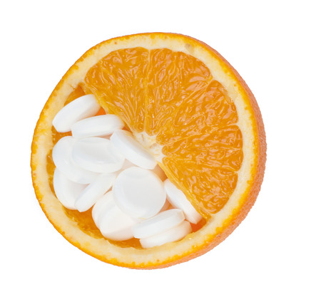 Close up of orange and pills isolated - vitamin concept. photo