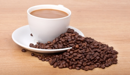 coffee cup and coffee beans on wooden background. photo