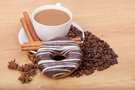 Coffee cup with coffee beans ans sweet cake on a wooden background. photo