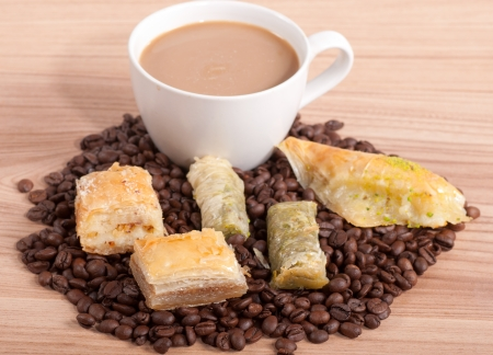 Coffee cup and coffee beans, sweets on the wooden background. photo