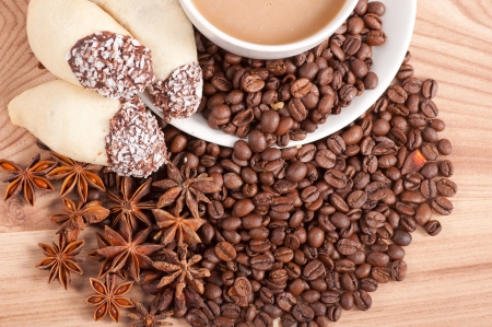 Coffee cup, anise on coffee beans, sweets on the wooden background. photo