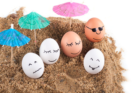 easter funny eggs under umbrella on a sand.