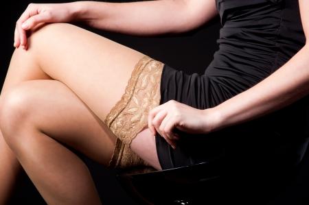 womans legs in black dress  over dark background. photo