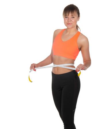 Beautiful slim woman measuring her waistline with a measuring tape. Stock Photo