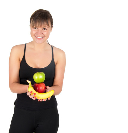 Beautiful fitness young woman with bananas and apples. Isolated on white background. photo