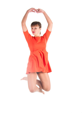 energetically: Cute young girl with red dress jumping energetically over white background.