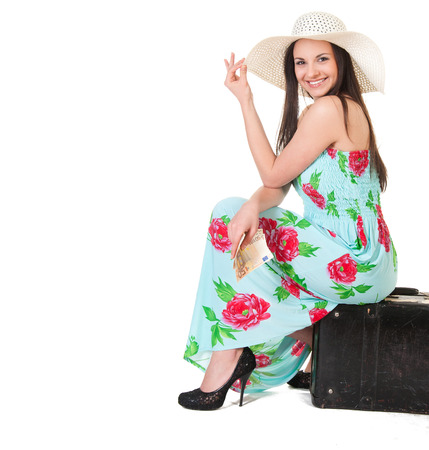 beautiful woman in summer dress with hat, case and money over white background photo
