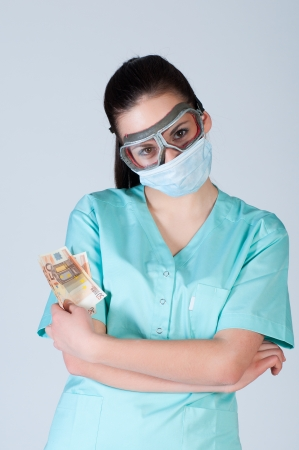 Nurse or doctor in pilot glasses with mask and money over gray background. corruption concept. photo