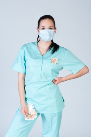 Nurse or doctor wearing  mask and holding money over gray background. corruption concept. photo